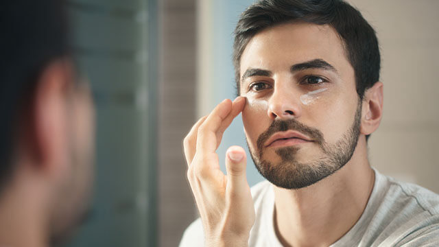 Hispanic male applying cream